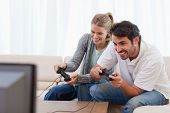 Cheerful couple playing video games in their living room