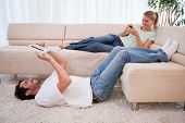 stock photo of dial pad  - Woman using her smartphone while her boyfriend is using a tablet computer in their living room - JPG