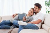 Lovely couple using a tablet computer in their living room
