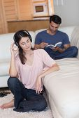 Portrait of a woman listening to music while her boyfriend is reading a book in their living room