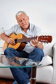 Senior man playing acoustic guitar at home
