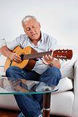 Senior hombre tocando la guitarra acústica en casa