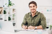 Young Businessman Smiling And Holding Pen In Modern Office poster