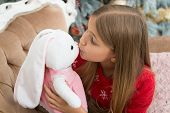 A Kissable Cutie. Small Girl Kiss Rabbit Toy. Little Girl With Cute Bunny At Christmas Tree. Little  poster