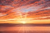 Dramatic, Fiery Yellow, Golden, Red And Magenta Sunrise Sky With Sun And Sun Rays Over The Sea. poster