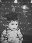 Smart Child In Graduate Cap On Serious Face, Shy, Holds Hands Crossed. Kid, Preschooler Or First For poster