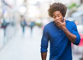 Afro american man over isolated background bored yawning tired covering mouth with hand. Restless an poster