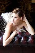stock photo of snob  - portrait of a beautiful fashion model wearing an elegant dress lying on the couch - JPG