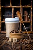 Take-out Mock-up Paper Cup With Coffee Beans And Sugar Crystal Stick On Rustic Wooden Background poster