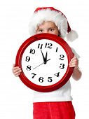 cute little girl in santa cap with a clock isolated oin white