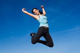 foto of athletic woman  - Attractive happy young woman jumping - sky background ** Note: Slight blurriness, best at smaller sizes - JPG