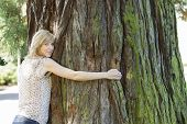 Young woman hugging large tree trunk