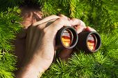 stock photo of spyglass  - a watching from the bushes with binoculars - JPG