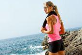 Fitness jovem mulher na beira-mar com toalha.