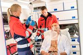 Paramedic putting oxygen mask on patient ambulance sick emergency