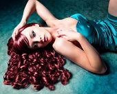 stunning woman with red hair and evening-dress lying on the floor