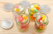 stock photo of parallelogram  - Colorful sweets in the four clear glass jars arranged parallelogram on wooden board - JPG