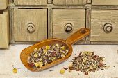 organic herbal tea (chamomile, peppermint,,orange peel, rose hips, hibiscus,) - rustic wooden scoop and a pile on rough white painted barn wood with a primitive apothecary drawer cabinet