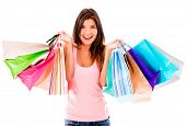 Female shopaholic holding a bunch of shopping bags - isolated over white