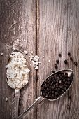 Vintage effect image of tarnished silver spoons filled with salt crystals and black peppercorns, ove