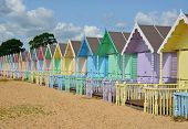 stock photo of chalet  - Long row of beach huts on the beach - JPG