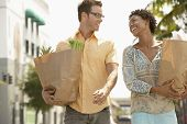 Happy multiethnic young couple with groceries walking outdoors