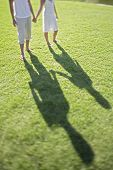 Low section of young couple holding hands while walking on grass at park