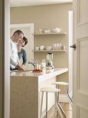 Happy couple standing at kitchen counter seen through open door