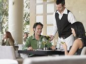 Waiter serving wine to young couple at outdoor restaurant