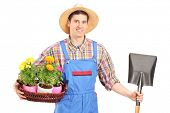 Male agricultural worker holding a shovel and flowers isolated on white background