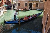 Italy, Venice - July 2012: Heavy Traffic Of Gondolas With Tourists Cruising A Small Canal On July 16