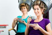 women at the hairdresser drinking coffee or cappuccino and chit-chat, while your hair drying under a
