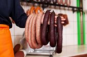 Sausages Hanging On Butcher's Hand
