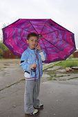 Little Boy Standing Under An Umbrella In The Spring