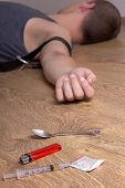 Spoon, Lighter, Syringe With Drugs And Addict Lying On The Floor
