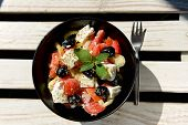 Salad with vegetables and feta cheese in black bowl