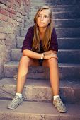 Sad Girl With Blue Eyes Sitting At Stone Brick Stairs