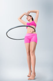 foto of hulahoop  - Young fitness sport woman rotating hula hoop low angle view - JPG