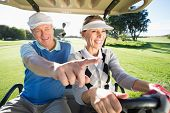 stock photo of golf bag  - Happy golfing couple sitting in golf buggy on a sunny day at the golf course - JPG