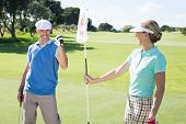 Lady golfer holding eighteenth hole flag for cheering partner on a sunny day at the golf course