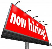 Now Hiring words on a big red outdoor billboard, sign or banner looking for workers