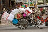 PHNOM PENH, CAMBODIA - MARCH 21: Plastic ware vendor driving his bicycle in Phnom Penh, Cambodia on