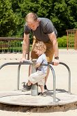 stock photo of merry-go-round  - Dad and son playing on merry - JPG