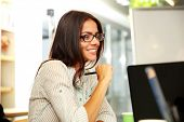 Portrait of a young smiling businesswoman in glasses at office