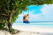 Woman in blue dress swinging at tropical beach