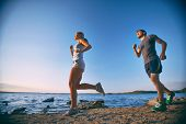 Photo of happy young dates running down coastline