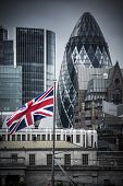 stock photo of phallic  - Focus on a Union Jack on the Thames with the city of London as a backdrop