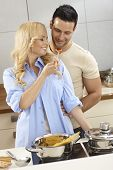 Loving couple hugging in kitchen, tasting spaghetti sauce, smiling.