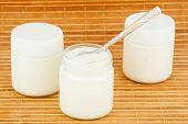 Three jars with home yogurt on a straw mat