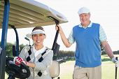 foto of buggy  - Happy golfing couple setting out for the day on buggy on a sunny day at the golf course - JPG